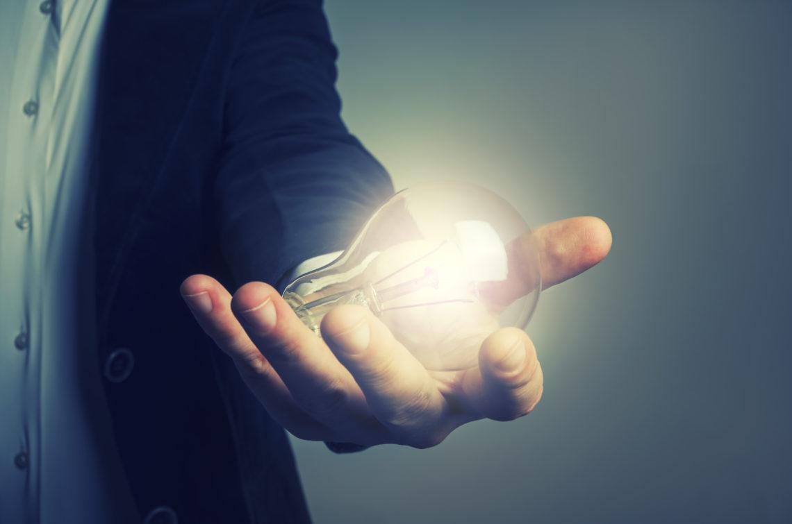 Mann hält eine leuchtende Glühbirne in der Hand