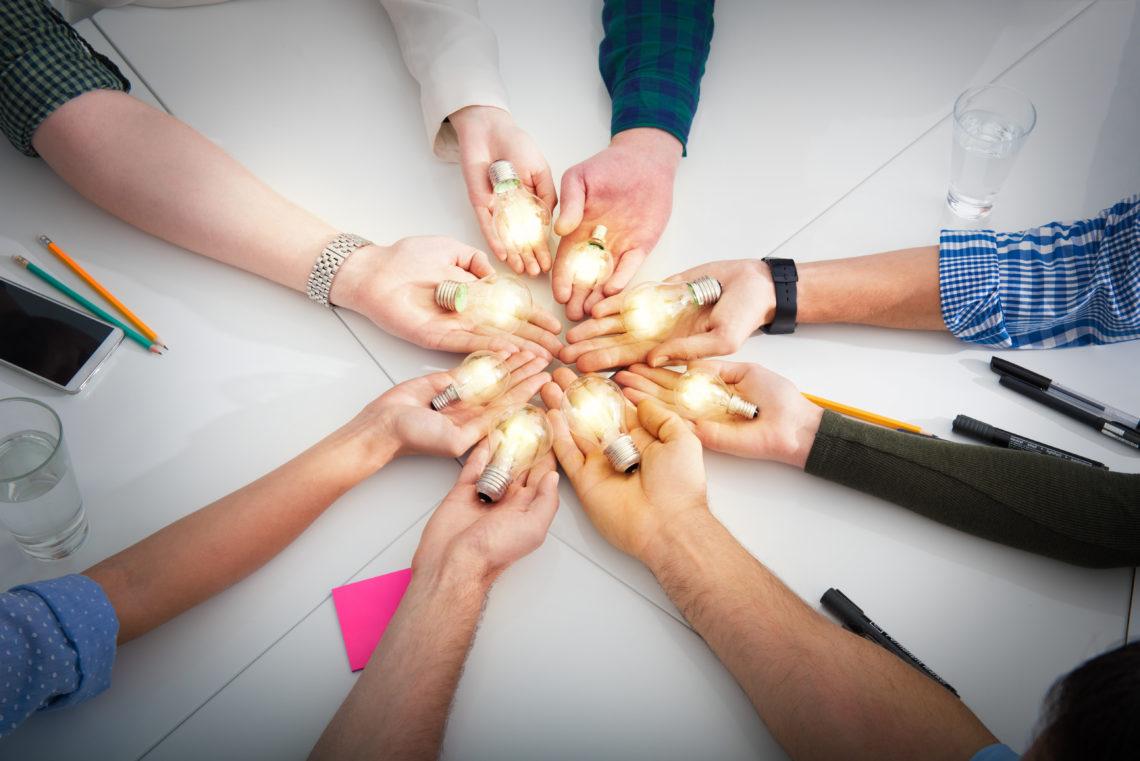 Viele Hände mit leuchtenden Glühbirnen