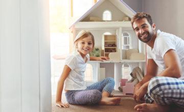 Mann und Tochter sitzen vor einem Spielzeughaus