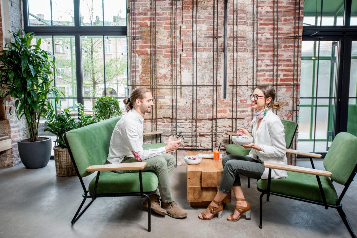 Zwei Menschen sitzen auf grünen Sesseln und reden