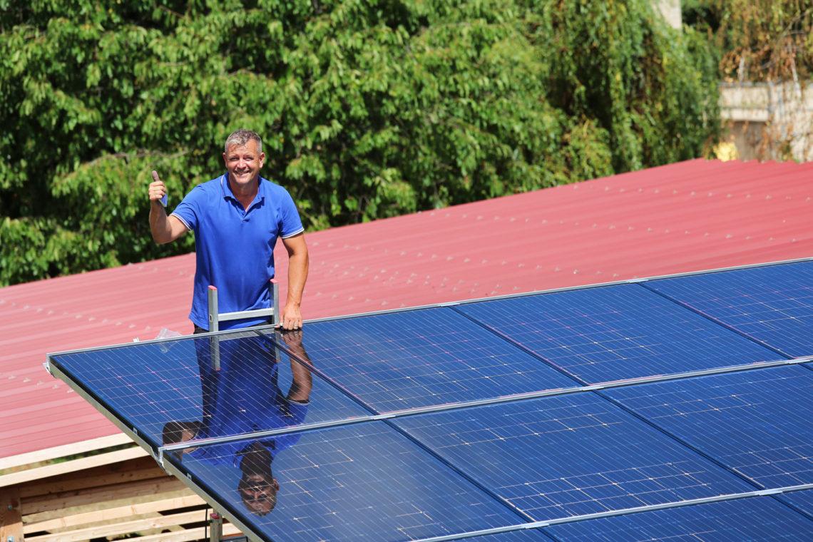 Glücklicher Mann auf Leiter betrachtet Photovoltaikanlage