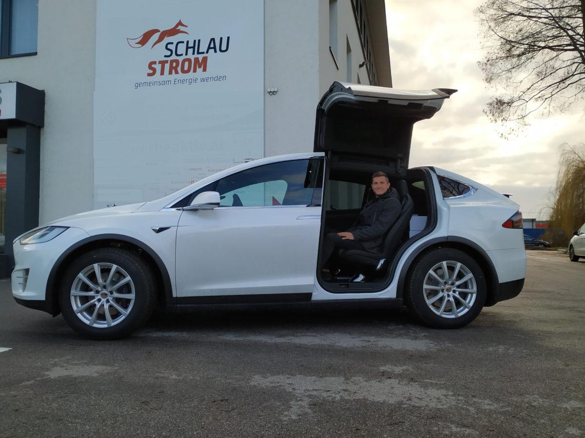 schlaustrom Mitarbeiter in einem weißen Tesla